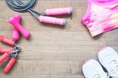 Плоское положение оборудований и аксессуаров спорта для женщины на деревянных предпосылке, красоте и здоровой стоковое изображение rf