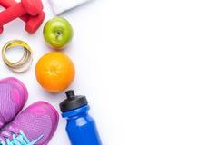 Плоское положение оборудования спорта Тапки, гантели, вода, полотенце, плодоовощи и телефон на белой предпосылке над взглядом Стоковые Изображения RF