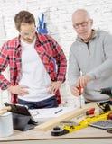 2 плотника работая в офисе, одном с отверткой Стоковое Изображение