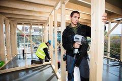 Плотники сверля древесину на строительной площадке Стоковая Фотография