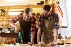 Плотники с планкой сверла сверля на мастерской Стоковое Фото