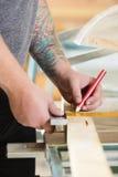 Плотник измеряет длину деревянной планки перед пилить Стоковое Фото