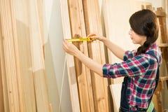 Плотник измеряя соответствующую древесину Стоковая Фотография