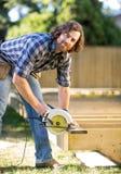 Плотник используя круглую пилу Стоковое Изображение