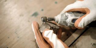 Плотник используя электрического точильщика руки стоковая фотография