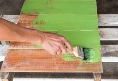 Плотник крася зеленый цвет к деревянной доске Стоковые Фото
