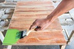 Плотник крася зеленый цвет к деревянной доске Стоковое Изображение RF