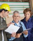 Плотник обсуждая с коллегами в мастерской Стоковые Изображения RF