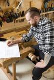 Плотник планирует проекты и принимает примечания на чертеже в мастерской Стоковая Фотография RF
