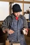 Плотник работая в мастерской плотничества стоковое фото
