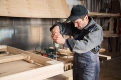 Плотник собирает деревянную мебель, фокус на сверле руки стоковые фото