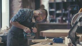 Плотник трудясь в маске и стеклах для безопасности Woodman с татуировкой видеоматериал