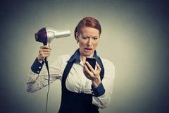 Плохая новость чтения женщины на smartphone смотря мобильный телефон держа фен для волос Стоковое фото RF