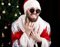 Плохое rastoman Санта Клаус держа сумку с подарками и царапая его бороду на предпосылке рождественской елки стоковое изображение