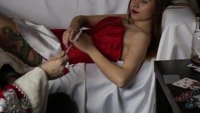 Плохой зверский Санта Клаус кладет впрыску лекарства для молодой сексуальной медсестры женщины в костюм масленицы шприц фокуса сн видеоматериал