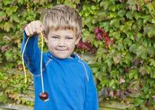 Плод конского каштана мальчика Стоковая Фотография RF