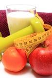 Плодоовощи, лента, молоко, зеленые гантели и фиолетовое полотенце на белизне Стоковые Изображения RF