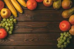 Плодоовощи на деревенской деревянной предпосылке как рамка Стоковое Изображение RF