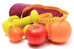 Плодоовощи, рулетка, зеленые гантели и полотенце на белизне Стоковые Изображения