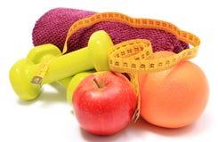 Плодоовощи, рулетка, зеленые гантели и полотенце на белизне Стоковая Фотография
