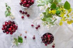 Плодоовощ вишни взгляд сверху свежий в стеклянной вазе, другие блюда с ягодами и опарник с жасмином и wildflowers на светлом мрам Стоковое фото RF