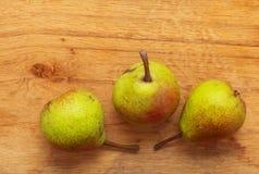 3 плодоовощ груш на деревянной предпосылке таблицы Стоковое Изображение
