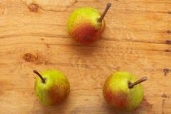 3 плодоовощ груш на деревянной предпосылке таблицы Стоковое Изображение RF