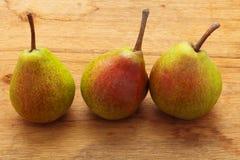 3 плодоовощ груш на предпосылке деревянного стола Стоковые Фотографии RF