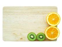 Плодоовощ и апельсин кивиа на деревянном блоке, изоляте на белизне Стоковые Изображения