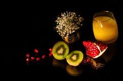 Плодоовощ и сок на стеклянной поверхности и черной предпосылке Стоковое Изображение RF