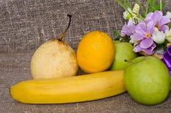 Плодоовощ и цветки на предпосылке холста Стоковые Изображения RF
