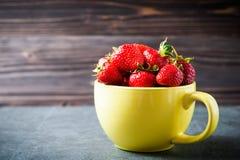 Плодоовощ клубники в желтой чашке на деревянной предпосылке Стоковое Изображение RF