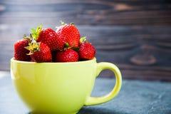 Плодоовощ клубники в желтой чашке на деревянной предпосылке Стоковые Фотографии RF