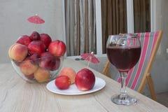 Плодоовощ на таблице Персики, нектарин, сливы стеклянное красное вино Стоковое фото RF