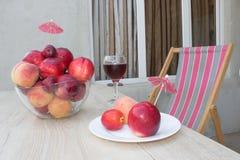 Плодоовощ на таблице Персики, нектарин, сливы стеклянное красное вино Стоковое Изображение