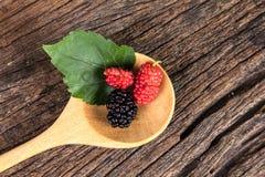 Плодоовощ шелковицы в деревянной ложке на деревянной плите Стоковое Фото