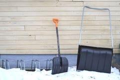 Плужок снега и снег копают склонность против стены Стоковые Изображения