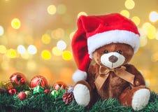 Плюшевый медвежонок в рождестве с шариком и подарочная коробка в нерезкости Backgroun Стоковая Фотография