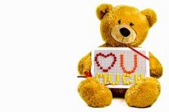 Плюшевый медвежонок держа лапки опознавания в влюбленности, положенной вне от мозаики ` s детей Стоковая Фотография