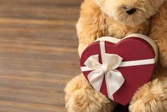 Плюшевый медвежонок держа подарок valentine's сердца на ба деревянного стола Стоковое Изображение RF