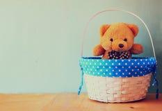 Плюшевый медвежонок игрушки в корзине на деревянном столе ретро фильтрованное изображение Стоковые Изображения RF