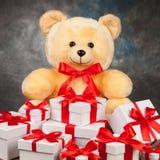Плюшевый медвежонок и белые коробки с подарками на старой доске Стоковое фото RF