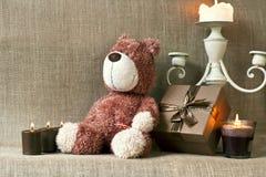 Плюшевый медвежонок и подарочная коробка с свечами на предпосылке мешка Стоковое фото RF