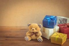 Плюшевый медвежонок и подарочные коробки на деревянной предпосылке стоковые фотографии rf