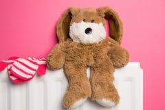 Плюшевый медвежонок и mittens Childs на радиаторе спальни Стоковые Изображения