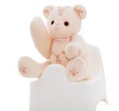 Плюшевый медвежонок на белом горшочке Стоковые Изображения