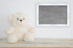 Плюшевый медвежонок на деревянном столе и классн классном Стоковая Фотография