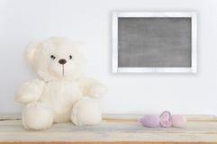 Плюшевый медвежонок на деревянном столе рядом с некоторым handmade amigurumi вычисляет Стоковое Изображение