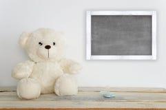 Плюшевый медвежонок на деревянном столе рядом с pacifier и классн классным Стоковые Фотографии RF