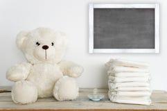 Плюшевый медвежонок на деревянном столе рядом с pacifier и некоторыми пеленками Стоковые Фото